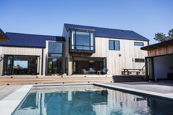 Bi-fold doors connect the main residence to the backyard, which features a large swimming pool, a 200-square-foot pool house, and an outdoor kitchen.