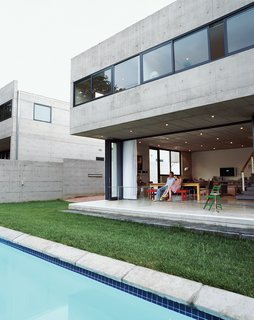 Gregory and Caryn Katz are dwarfed beneath the cantilevered concrete overhang, which houses the bedroom on the upper level. The stackable glass doors that run beneath allow the house to open completely to the yard and swimming pool, soften the severity of the concrete, and blur the boundary between indoors and out.