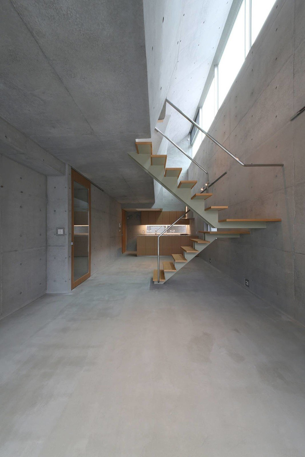 The interior consists entirely of exposed concrete accented by wood. The ground floor features double-height ceilings that maximize natural light from the light wells above.