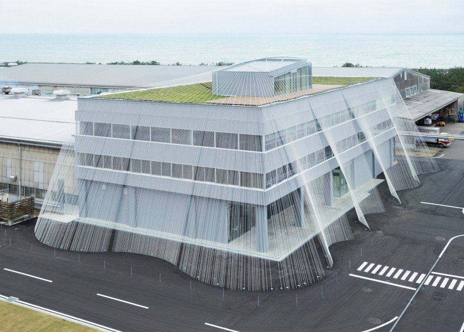 This  office building was renovated in rigid-frame RC structure to strengthen its earthquake resistance by using carbon fiber, and transform the interior into a museum called Fab Labo, a space to display the technology of Komatsu Seiren, the client company. Drawing inspiration from a technique of braiding ropes indigenous to this part of Japan, the fiber rod is said to be ten times stronger than iron, and is the very first time that this material was used as a means of reinforcement against earthquakes. The potential of this light and soft fiber is explored inside the building as well. There is a lighting duct in fiber and on the rooftop, an experimental greening is being conducted using porous ceramic panels (called Greenbiz), which was generated from the process of producing fiber.