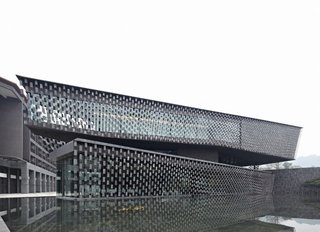 Locally-made tiles that are fixed tightly with stainless-steel wires create a curtain that covers the facade.