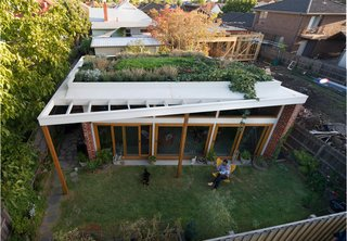 These 10 Green Roofs Bring Life—and So Much More—to These Modern Structures - Photo 1 of 11 - Emilio Fuscaldo sits in the garden outside the brick house that he designed for himself and his partner, Anna Krien, on a small subdivided lot in Coburg, a suburb north of Melbourne, Australia.