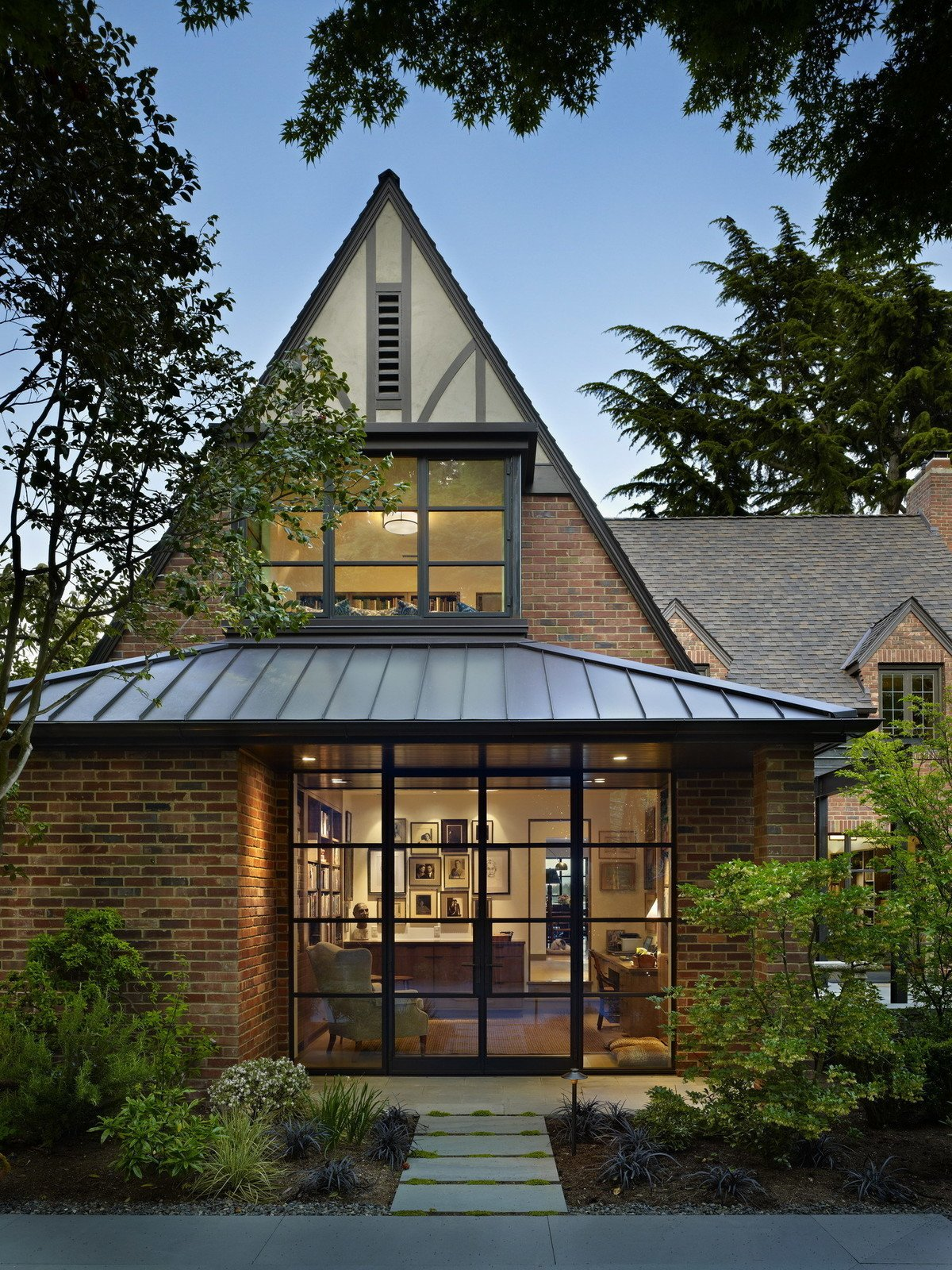 This whole-house remodel gives a venerable brick Tudor home a modern twist. Designed for two book (and dog!) lovers, it incorporates bookshelves and cozy seating areas throughout the house. Modern details complement traditional elements while steel windows, doors and exposed structure open the interior to light and views. The exterior features a 'secret garden', sunroom and terrace that overlook Lake Washington.