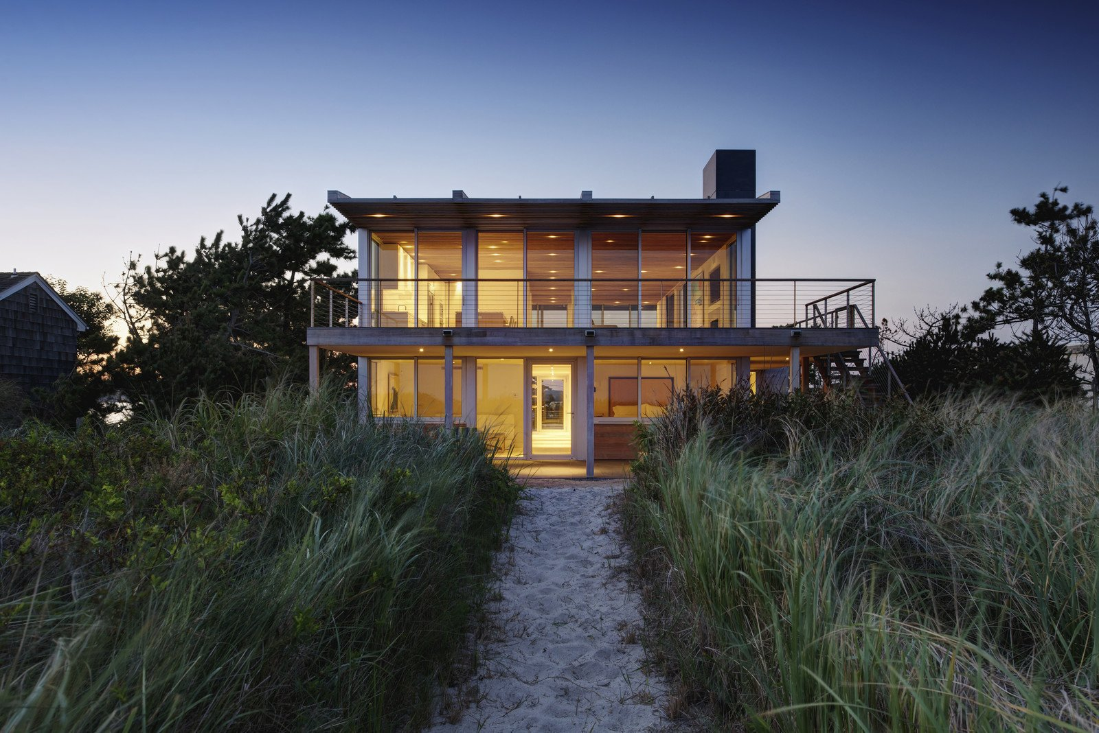Perched atop the crest of the dune between the ocean and bay, this home in the Hamptons utilizes elegant materials which were chosen for their simplicity, sustainability, low maintenance and ability to coexist with the sea, sand and vegetation of the site. The use of glass also provides the residents with stunning views of their surroundings.   <span style=