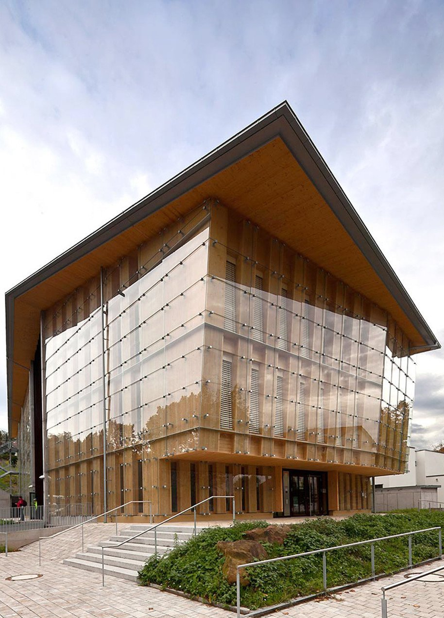 The Farmers' House in Freiburg, Germany, showcases natural wood and glass. The double imbricated glass facade showcases a highly weather proof glass frontage and allows for fascinating light reflections. Glass Takes Center Stage in These 10 See-Through Homes - Photo 7 of 11