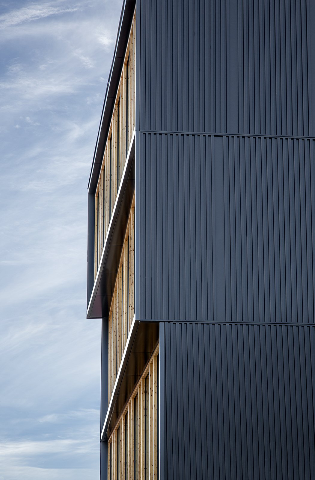 The facade cantilevers out four feet with a four inch thick panel. Albina Yard—Pioneering the Future of Sustainable Mass Timber Construction - Photo 7 of 9