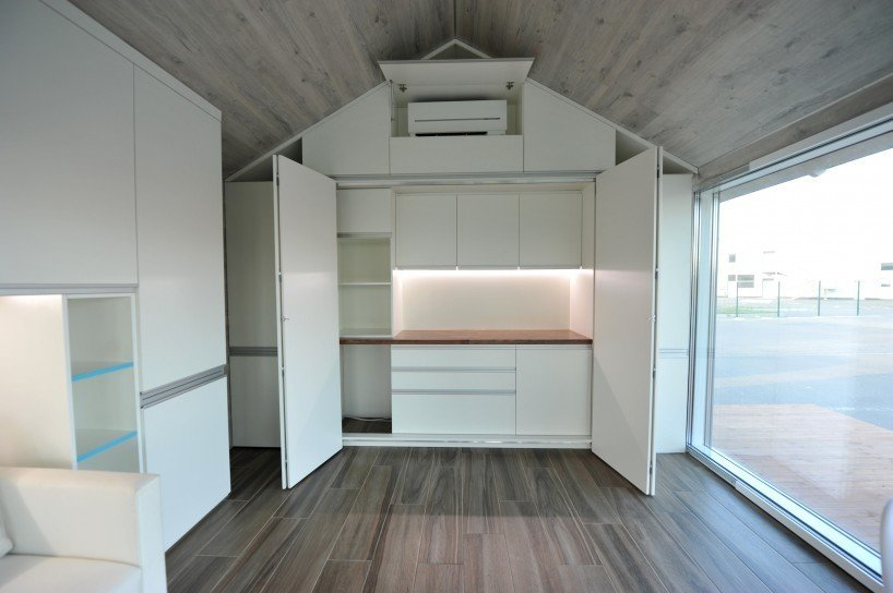 The house produces electricity for all the household appliances and even features an independent sewage system. Tagged: Front Yard, Table, Trees, Chair, Grass, Sofa, Ceiling Lighting, Light Hardwood Floor, and Storage Room.  Photo 5 of 6 in This Zero-Energy Passive Mobile Prefab Was Partially 3D Printed