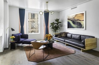 A large custom-made leather sofa from Wherewithal defines the living room, making it a comfortable space for entertaining. The Cloud One Seater lounge chair by Luca Nichetto and a Bellevue Floor Lamp by Arne Jacobsen form a perfect reading spot near the window, offering views of Brooklyn's neighboring brownstones.