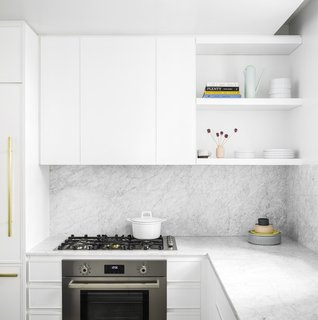 The white minimalist kitchen is fully outfitted with premium Bertazzoni Italia and Bosch appliances. It also features Italian Cararra marble countertops, an island, custom-designed cabinetry, and natural brass Fantini fixtures.