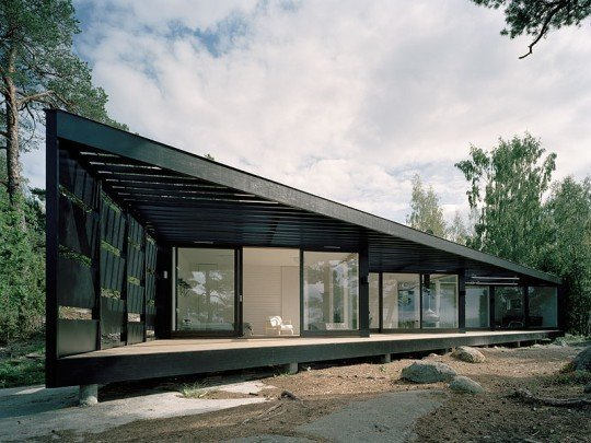 """A Look at 10 Minimalist Scandinavian Cabins - Photo 5 of 10 - A light-weight building in glass and wood, this summer house in the Stockholm archipelago has been inspired by its location. A dark wood exterior, strong vertical presence, and abundance of windows help integrate the residence into its surrounding environment. <span style=""""color: rgb(204, 204, 204); font-size: 13px;"""">Tham & Videgard Hansson Arkitekter</span>"""