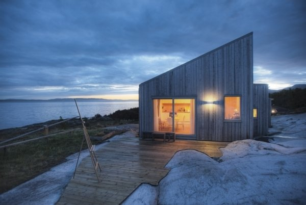 Designed by TYIN tegnestue Architects and built by the owners themselves, this cottage celebrates traditional back-to-nature elements in traditional Norwegian culture. Situated amidst marshland, sea-adjacent rock and scattered pine-and juniper-vegetation, careful consideration was made to protect the sensitive surrounding terrain. Only 328 feet from the sea, some marsh had to be cleared in preparing for the construction, exposing bedrock and integrating the cottage within the landscape.
