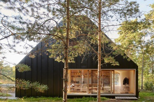Nestled in a forest of tall pines in the Stockholm Archipelago, the exterior of this island home is clad entirely in folded black sheet metal. Three glazed sliding doors with hardwood frames provide entrances and direct access to the outdoor areas.  Photo 7 of 10 in A Look at 10 Minimalist Scandinavian Cabins