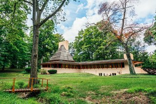 """10 Frank Lloyd Wright Homes Available to Rent Right Now - Photo 10 of 10 - The Dr. Richard Davis House, also known as """"Woodside,"""" is situated on a wooded two-acre lot in an established and conveniently located neighborhood in Woodside, Indiana. This unique home, which is on the National Registry of Historic Places, was built in 1952 and has been completely renovated by the current owner."""
