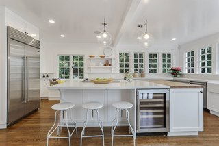 With an Architectural Pedigree and Green Certification, This Pasadena Home Just Listed For $3.6M - Photo 1 of 10 - The bright and spacious kitchen is full of windows which blend indoors and outdoors. The updated space, which merges historic architecture with modern features, showcases a butler's pantry, breakfast alcove, and deck access for outdoor dining.