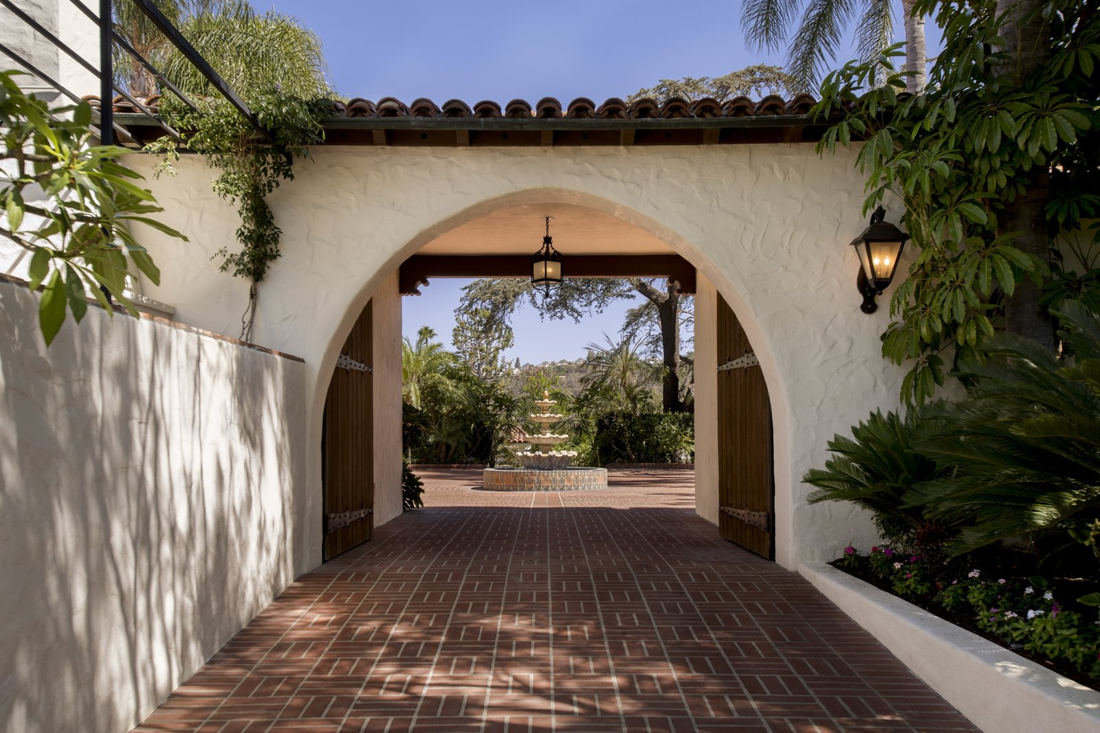 Historic charm abounds throughout the property with terracotta tiled arches and white stucco walls.  Photo 2 of 9 in Just Listed at $4M, This Spanish Colonial Revival in Southern California Promises Resort-Like Living