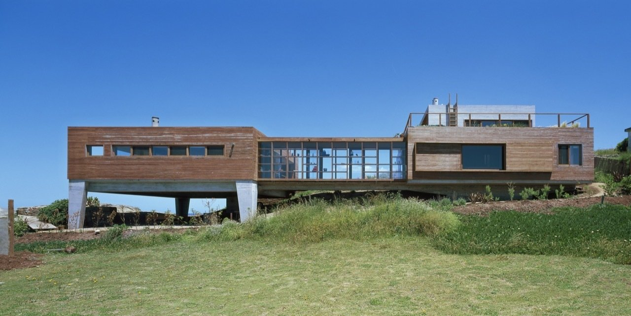 Built from Ipe and exposed concrete, this holiday refuge appears to be emerging from the rocks of its rugged seaside landscape. Located in a fishing village 50 miles north of Punta del Este, on the Atlantic Ocean, the double sloped site of La Roca House is edged by rocks and the remains of the foundation of a pre-existing building which now forms a natural garden of succulents. The home is defined through a sequences of spaces, which consist of two modules of the same height, generating two patios in their voids. The main volume was designed for the social space, and the second for the family's private space—and includes a master bedroom with a stunning panoramic view of the surroundings.