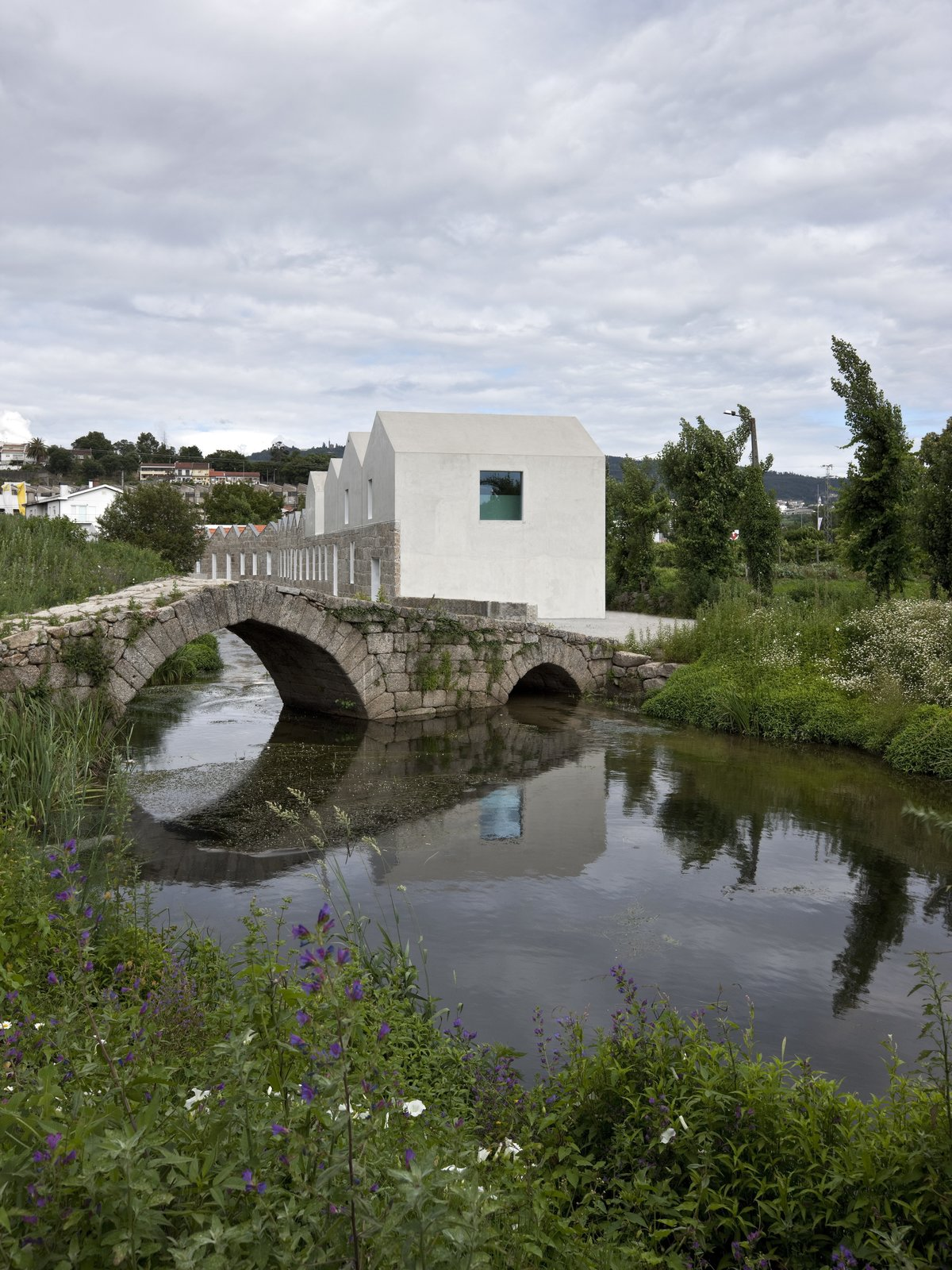 Located in Guimaraes, Portugal, the Porto-based firm Cannatà e Fernandes took sections of this nineteenth-century stone factory which were beyond repair and replaced them with white concrete for this thoughtful rebuild.  Photo 5 of 17 in A New Book Examines the Art of Breathing Life Into Forgotten Architecture