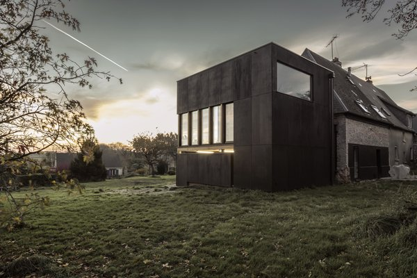 The extension of this early twentieth-century home in Senneville-sur-Fécamp, France, Ziegler Antonin Architecte left the main house untouched--adding a dark rectilinear structure which contrasts the original light brick home creating a total escape for the homeowners in the form of a light-filled library.