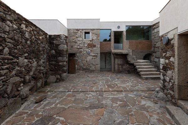 Brandão Costa Arquitectos placed concrete atop the original stone mass to fill-in existing irregularities and create a new clean roofline for this renovation in Caminha, Portugal.  Photo 11 of 17 in A New Book Examines the Art of Breathing Life Into Forgotten Architecture