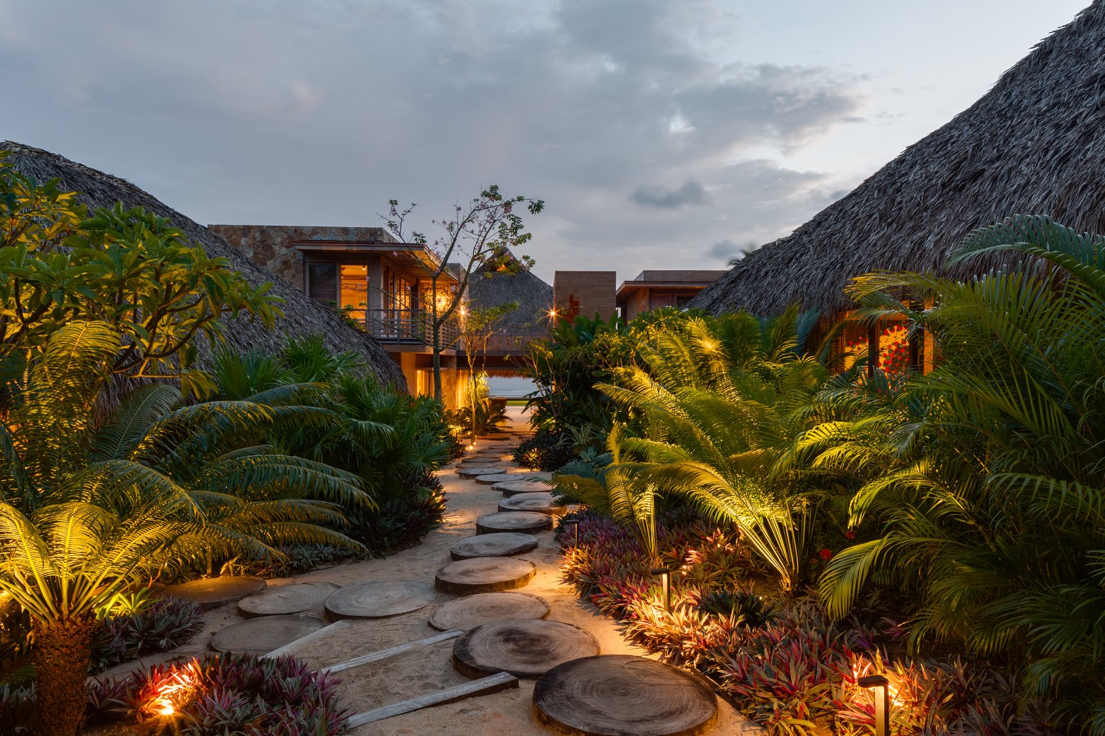 Each of the smaller pavilions is nestled in the landscape of native vegetation and set along a path connected by stepping stones made of cut tree trunks. Tagged: Outdoor, Side Yard, Trees, Walkways, and Landscape Lighting.  Photo 2 of 14 in This Expansive Beachside Home on Mexico's Pacific Coast Puts a Modern Spin on Tradition