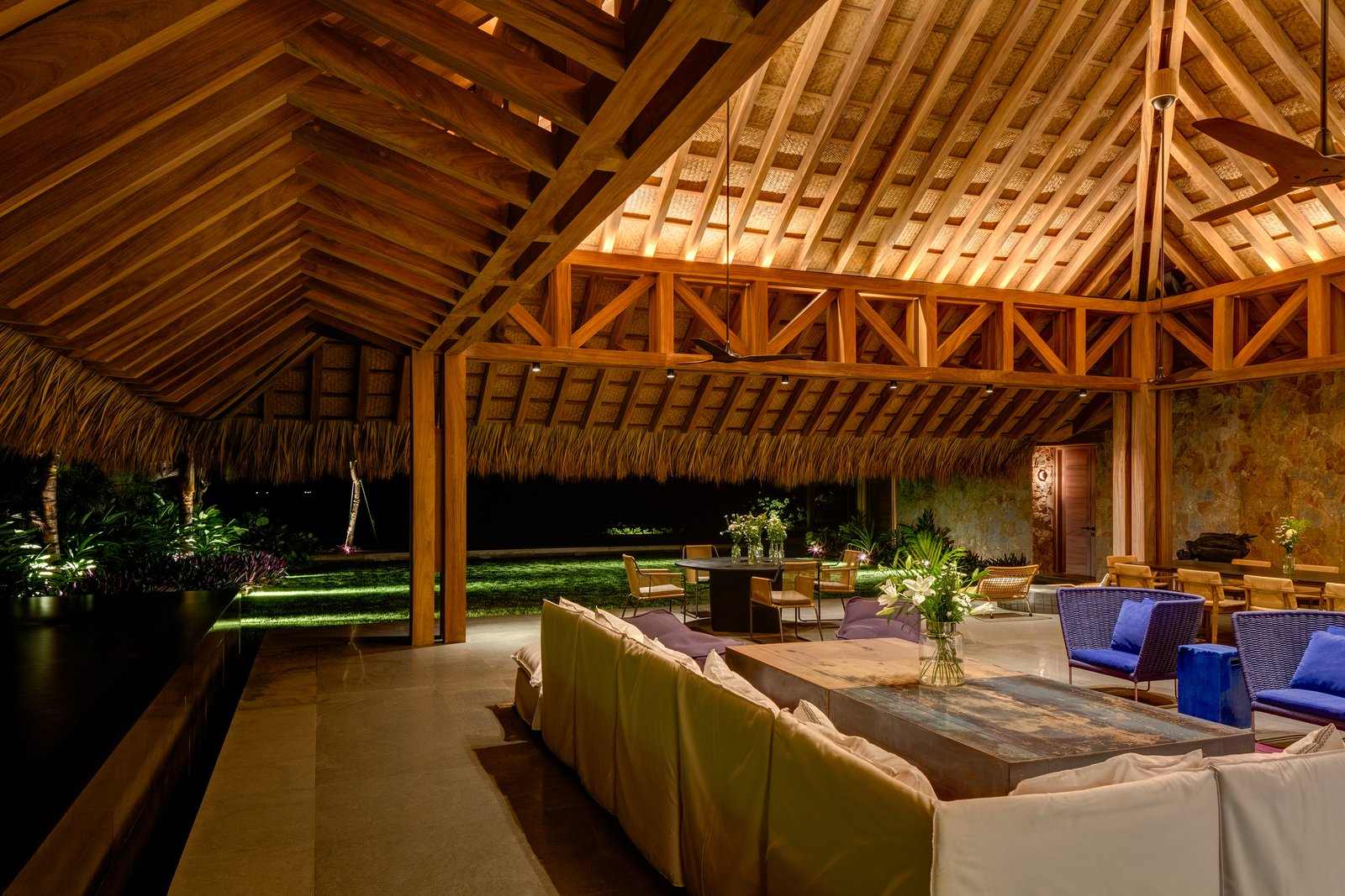 The living/dining area is in a palapa made of natural parota wood which is over 33 feet high. Tagged: Living Room, Chair, Ceiling Lighting, Cement Tile Floor, Sectional, and Coffee Tables.  Photo 5 of 14 in This Expansive Beachside Home on Mexico's Pacific Coast Puts a Modern Spin on Tradition