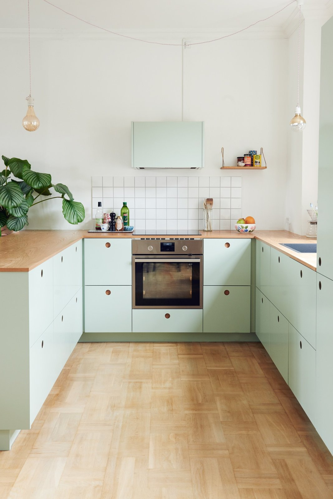 Danish blogger, Tikkie Elsøe, chose mint green Tagged: Kitchen, Wood Counter, Light Hardwood Floor, Pendant Lighting, Subway Tile Backsplashe, Wall Oven, Range Hood, Drop In Sink, Colorful Cabinet, and Cooktops.  Photo 4 of 9 in Modern Kitchen Upgrade Ideas From a Danish Design Firm That's Challenging the Kitchen Market