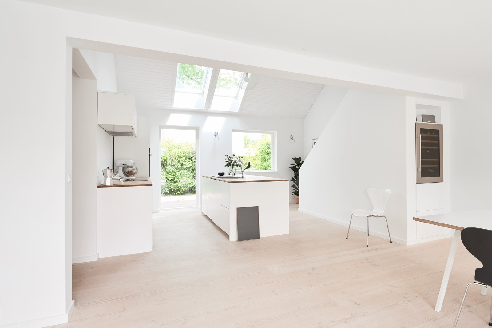 Henning Larsen Architects' design was used in spray painted white with painted metal bands that have been painted the same color and oak counter tops for this bright and airy contemporary home in Charlottenlund, Denmark.