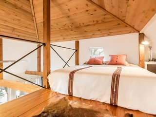 Feel at Home While Exploring Austin at One of These Modern Short-Term Rentals - Photo 16 of 17 - It's an open space with a cathedral ceiling and exposed-cedar beams. There's a queen-sized bed on the main level and another in the loft area.