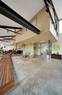 A 1960s Melbourne Warehouse Is Upcycled and Transformed Into an Energy-Efficient Family Home - Photo 4 of 11 - Mezzanine-level rooms float within the original volume of the warehouse. The existing floor slab was also preserved, partially due to restricted site access, but also for its inherent character.