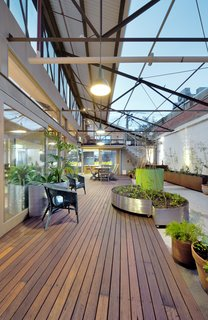 A 1960s Melbourne Warehouse Is Upcycled and Transformed Into an Energy-Efficient Family Home - Photo 10 of 11 - To overcome the waterproofing issues that come with having an internal courtyard, a hob was created around the perimeter and a new slab was constructed that drains water out to a central storm-water pit. The raised hob and slab are disguised by a new recycled timber deck that straddles the interior and exterior spaces, blurring the transition between the indoor and outdoor areas. Movable planter boxes made out of Cor-Ten steel were introduced to create a garden.