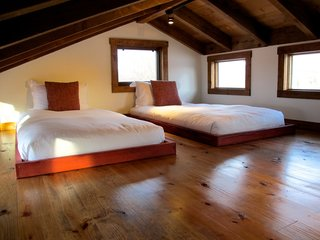 Test Out Tiny House Living at One of These Nature-Immersed Cabin Resorts - Photo 4 of 14 - A lofted bedroom with a pair of simple, low beds
