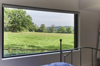 Historic Gasworks Cottage With a Modern Cor-Ten Steel Addition Hits the Market - Photo 7 of 9 - The master bedroom suite boasts a large picture window with far-reaching rural views.