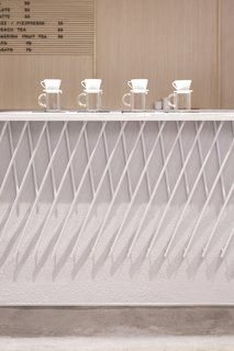 A Sleek Coffee Shop in Hong Kong With Beautiful, Minimalist Interiors - Photo 3 of 9 - The front of the coffee bar features a decorative armor made out of angled pieces of white-painted metal that form a criss-cross pattern.
