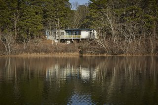Experience Cape Cod Modern by Staying at the Midcentury Weidlinger House - Photo 1 of 8 - Anchored on concrete piers at the higher end of the slope, the house shoots out over stilts, suspended in midair for a commanding view of Higgins Pond.