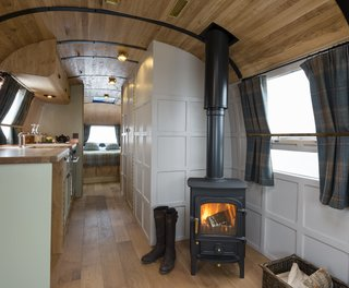 Live the Airstream Life Vicariously With a New Book That Celebrates the Timeless Trailers - Photo 10 of 19 - Called the English country retreat, this renovated interior that was done by ARC Airstreams features quality furnishings and fttings, Leadlight windows, and a fully functional fireplace.