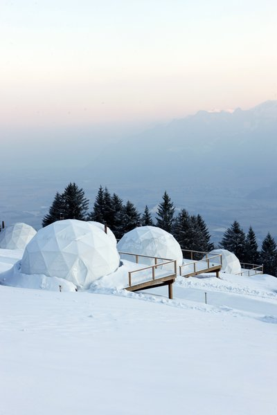 The geodesic domes look like igloos in the snowy Alpine landscape.
