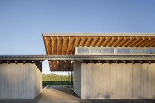 6 Modern Wineries on the West Coast With Beautiful Architecture - Photo 3 of 17 - Inspired by the canopied, native oak trees that populate the valley, two cantilevered roof structures interlock at the tasting room's entryway. The material palette is limited to Douglas fir, exterior-cedar siding, and dark-anodized aluminum.