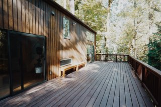 """This Tree House For Rent Near Downtown Portland Doubles As an Art Platform - Photo 7 of 14 - The double-height living room opens to a spacious outdoor deck nestled in the forested """"backyard."""""""
