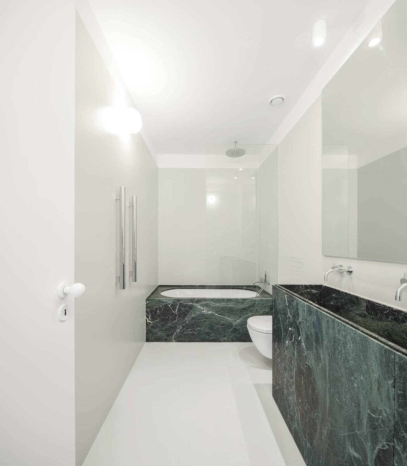 Tagged: Bath Room, Undermount Sink, Undermount Tub, Stone Counter, Ceiling Lighting, Wall Lighting, One Piece Toilet, Open Shower, and Marble Counter.  Best Photos from A Luminous Renovation in Portugal Creates a Bright and Airy Apartment