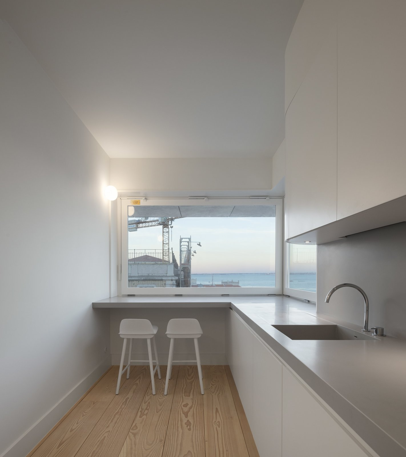 Tagged: Kitchen, Drop In Sink, Light Hardwood Floor, and Wall Lighting.  Best Photos from A Luminous Renovation in Portugal Creates a Bright and Airy Apartment