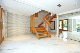 An Airy Toronto Estate For Sale Boasts Excellent Feng Shui - Photo 2 of 13 - The entrance features marble floors and a grand staircase. The home was built with sturdy 2x6 construction and features plastered walls throughout.