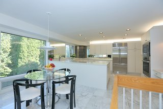 An Airy Toronto Estate For Sale Boasts Excellent Feng Shui - Photo 7 of 13 - The bright and open contemporary kitchen leads out to the back patio.