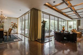 A Frank Lloyd Wright-Inspired Waterfront Masterpiece in Dallas Is Up For Auction - Photo 3 of 15 - A series of sliding doors frame the exterior landscape and lead out to the patio.