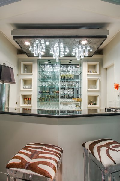 A bar area showcases custom-made cast lighting and built-in cabinetry.