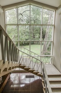 A Frank Lloyd Wright-Inspired Waterfront Masterpiece in Dallas Is Up For Auction - Photo 10 of 15 - A grand staircase leads to the second level the home also features an elevator.