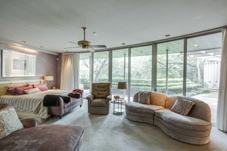 A Frank Lloyd Wright-Inspired Waterfront Masterpiece in Dallas Is Up For Auction - Photo 11 of 15 - Designed for privacy, the master suite features giant sectional sliding doors and windows along with a unique geometric curved layout.