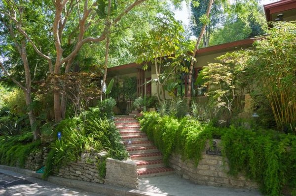Brick stairs lead to the entrance of the midcentury abode. Tagged: Exterior, Mid-Century Building Type, and Flat RoofLine.  Green Living by Eran Falk from Anna Faris Lists Her Midcentury Abode in the Hollywood Hills For $2.5M