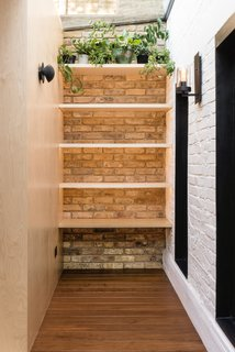 A Crafty Triangular Addition Carves Out Office Space in a London Backyard - Photo 6 of 11 - The walls are made of exposed bricks in reference to the original Victorian house.