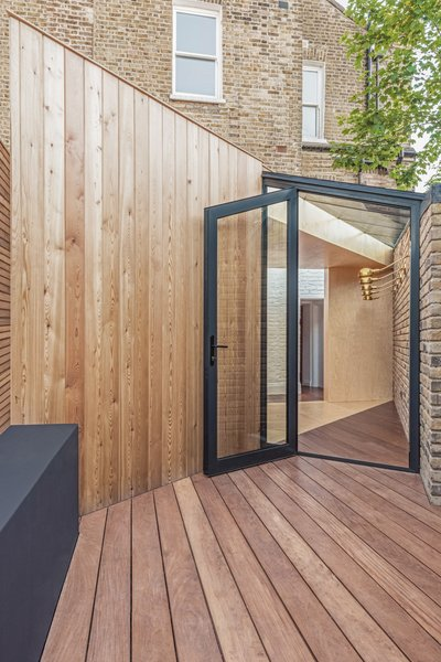 The patio area floor is finished with a dark-stained decking, surrounding and contrasting the pale-colored plywood.