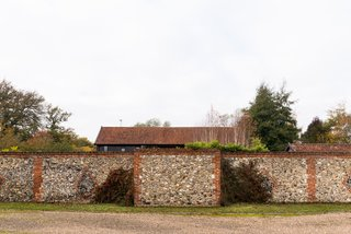 This Spectacular Suffolk Barn Conversion Hits the Market at $1.26M - Photo 3 of 13 - An exterior stone wall surrounds the property.